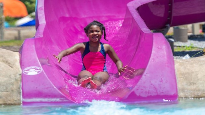 girl coming out of purple slide