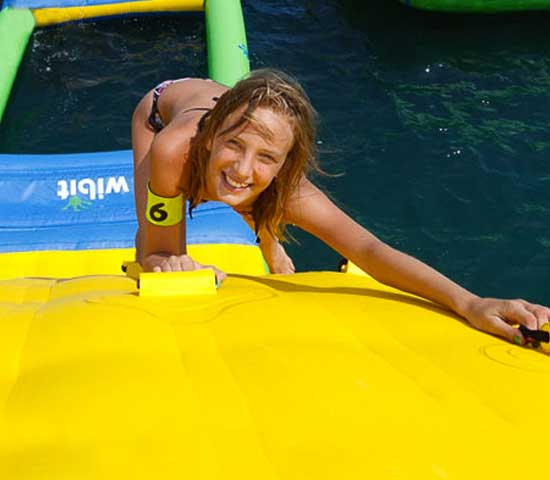 Girl climbing on inflatable wall over Adventure L