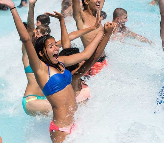 Group of kids jumping waves in the wave pool
