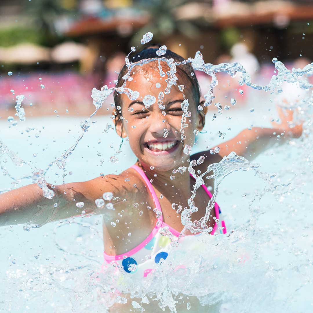 Young girl splashing in wave pool
